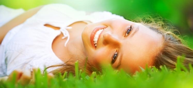 szczęśliwa kobieta leząca na trawie